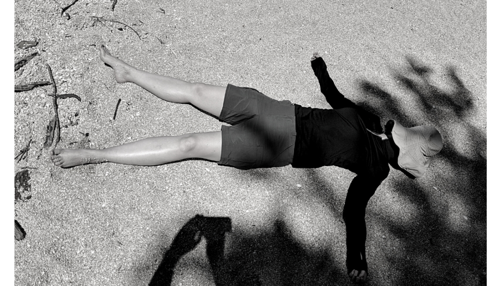 woman lying down in the sand with hat on her face